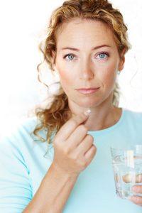 Vrouw met MenaQ 45 mcg vitamine K2 menaquinone-7 tablet